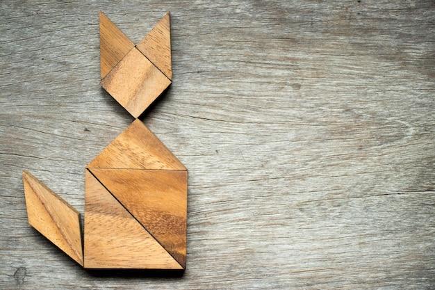 Puzzle de tangram en forme de chat sur fond en bois