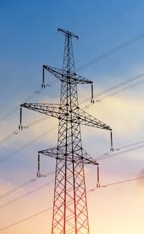 Pylône électrique silhouetté sur fond de ciel bleu