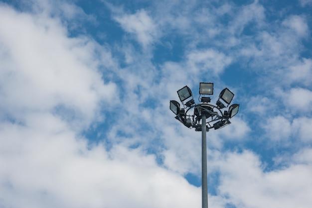 Pylône lumineux haut mât sur ciel nuageux