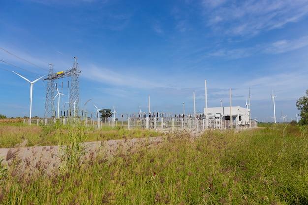 Pylônes électriques et centrale ou station avec éolienne en pleine nature