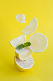 Pyramide de citron haché en équilibre sur fond jaune. emplacement vertical.