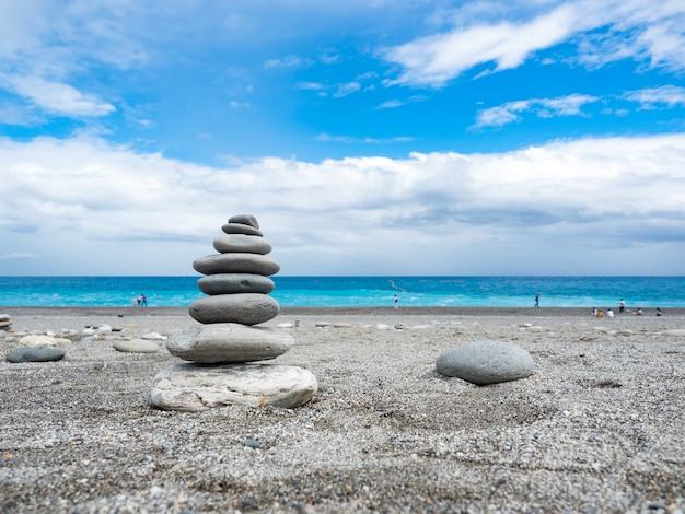 Pyramide de galets de mer sur une plage de sable ensoleillée à hualien, taiwan.