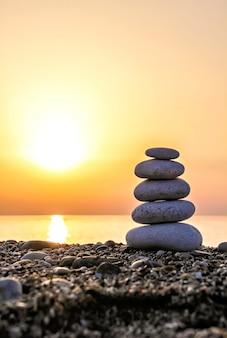 Pyramide de pierre zen sur la plage au coucher du soleil