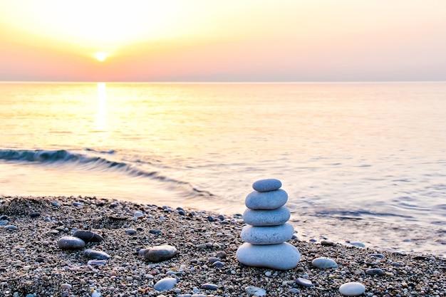 Pyramide de pierre zen sur la plage au lever du soleil