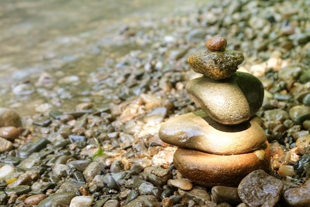 Pyramide de pierres dans le style japonais sur la berge de la rivière méditation relax sérénité