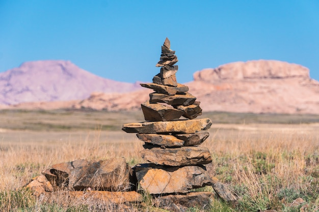 Pyramide de pierres sur le fond de crêtes dans les steppes du kazakhstan