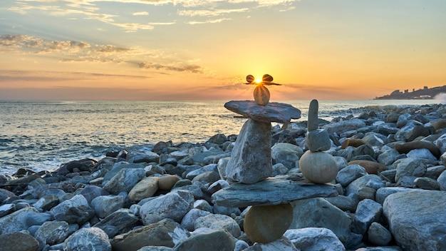 Pyramide des pierres isolées sur fond de coucher de soleil, bord de mer