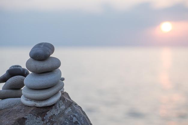 Pyramide de pierres sur sable symbolisant le zen, l'harmonie, l'équilibre.