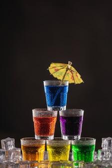 Pyramide de plans avec de l'alcool coloré, décorée de parapluies pour cocktails