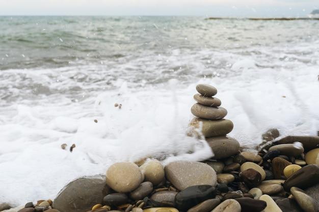 Une pyramide de rochers en équilibre sur la plage pendant une tempête