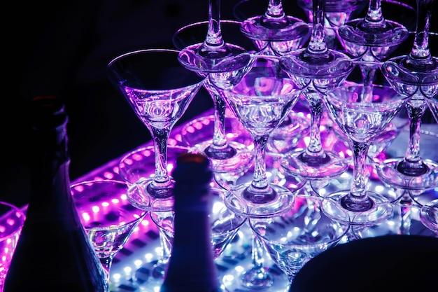 Pyramide de verres à champagne pour fête formelle ou mariage. la cérémonie pour la décoration des vacances est la tour de champagne. design de luxe pour les événements. contexte parfait pour la créativité. espace copyright pour le site