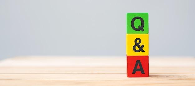 Q et un mot avec bloc de cube en bois. faq (fréquence des questions), réponses, questions posées, informations, communication et concepts de remue-méninges