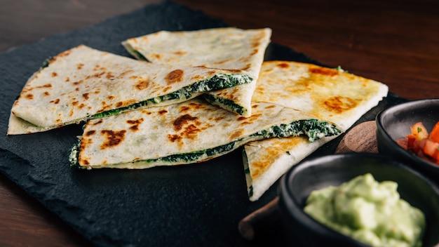 Q quesadillas au fromage et aux épinards cuits au four, servies avec salsa et guacamole.