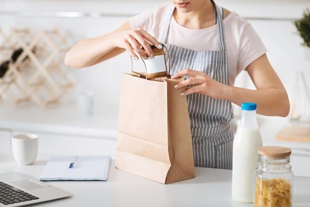 Qu'avons-nous là. belle jeune femme prudente sortant les produits alimentaires du sac en papier et les triant debout à la table dans la cuisine