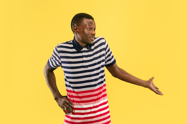 Qu'est-ce que c'est. jeune homme afro-américain isolé sur fond de studio jaune, expression faciale. beau portrait d'homme mi-long. concept d'émotions humaines, expression faciale. l'air surpris.