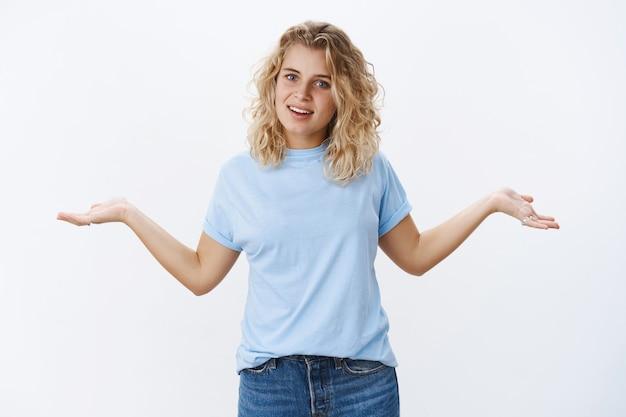 Qu'est-ce que tu vas faire. petite amie en colère énervée aux cheveux blonds se disputant, debout, irritée, haussant les épaules, les mains écartées sur le côté dans une pose difficile, interrogée et confuse