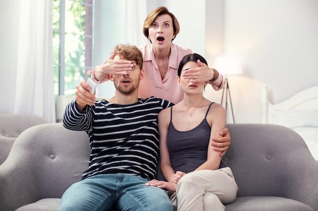 Qu'est-ce que vous regardez. agréable femme émotionnelle debout derrière le couple et fermant les yeux tout en contrôlant ce qu'ils regardent