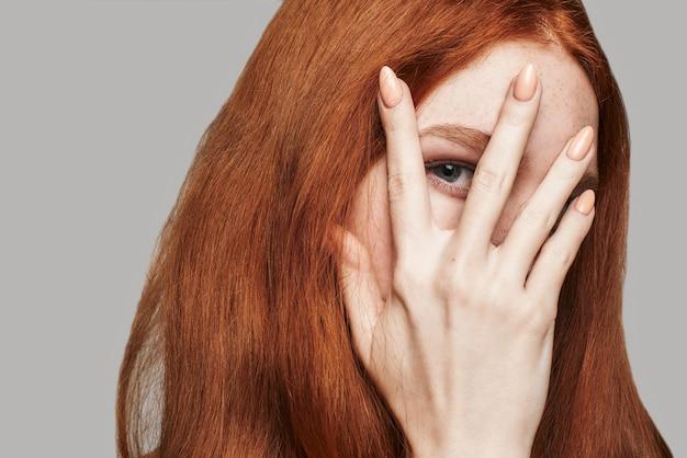 Qu'y a-t-il en gros plan sur une jeune et belle femme aux cheveux rouges et soyeux