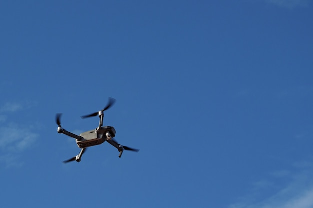 Quadcopter de drone avec appareil photo numérique, drone planant dans le ciel bleu