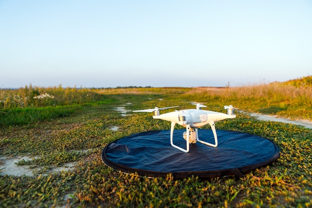 Quadcopter drone survolant le champ vert en été. l'innovation technologique dans l'industrie agricole