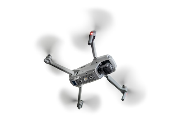 Un quadcopter volant est isolé sur un fond blanc.
