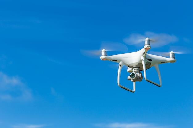 Quadricoptère de drone volant avec appareil photo numérique sur ciel bleu