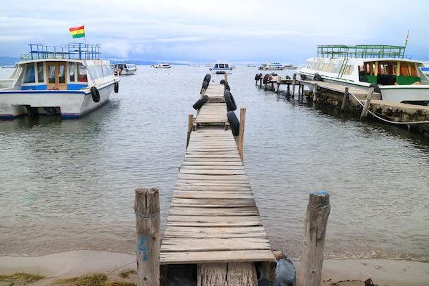 Quais en bois entourés de bateaux à isla del sol sur le lac titicaca dans la ville de copacabana, en bolivie