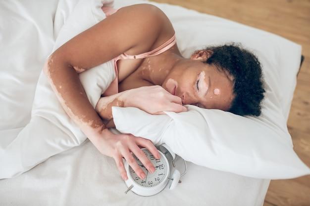 Qualité du sommeil. une femme à la peau foncée allongée dans son lit et ayant l'air endormie
