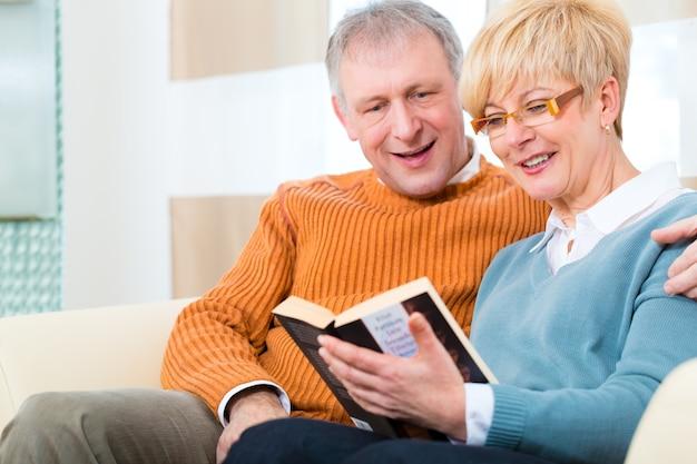 Qualité de vie - deux personnes âgées assises à la maison sur le canapé, il embrasse sa femme