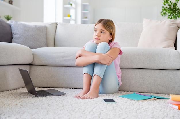 Quand on va à l'école. photo pleine grandeur d'une fillette frustrée étude fatiguée à distance du virus corona covid mise en quarantaine regarder imaginer l'infection arrêter de se propager s'asseoir tapis de sol dans la maison à l'intérieur