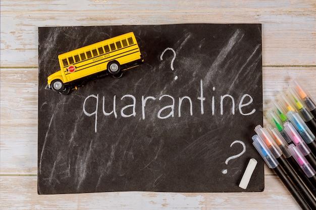 Quarantaine à l'école pour le concept de l'élève. tableau noir, crayons et jouet de bus.