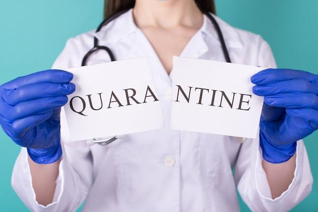 La quarantaine est sur le concept de liberté des personnes libres. photo recadrée en gros plan d'une femme médecin en gants tenant des parties de papier de quarantaine isolées sur fond bleu sarcelle