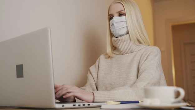 Quarantaine. isolement, éloignement social, travail indépendant à domicile, auto-isolement. jeune femme d'affaires en masque médical jetable tape sur le clavier d'ordinateur portable et écrit. coronavirus.