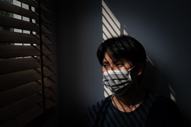Quarantaine de personnes à risque pour empêcher la propagation du covid-19, homme portant un masque et regardant par la fenêtre à la maison, virus corona. coronavirus de wuhan et symptômes du virus épidémique et protection