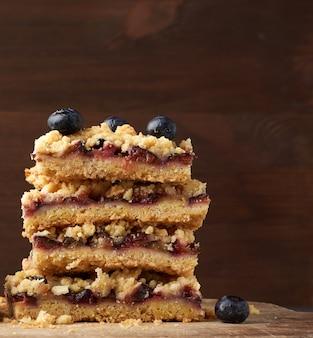 Quare tranches de tarte au crumble au four avec prune bleue sur une planche de bois