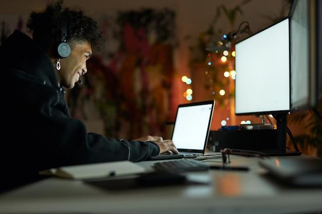 Quart de nuit souriant jeune homme portant un casque assis à la table devant des écrans d'ordinateur