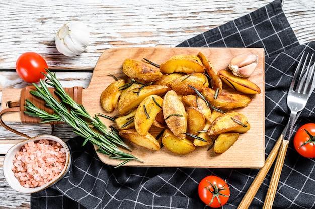 Quartiers de pommes de terre frites, frites sur une planche à découper en bois. fond blanc. vue de dessus