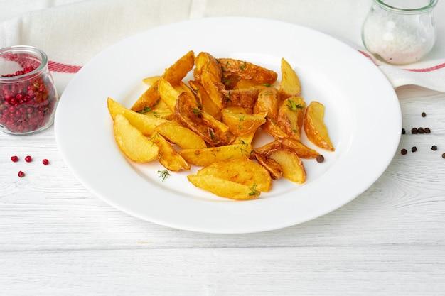 Quartiers de pommes de terre frites en plaque sur table en bois blanc close up