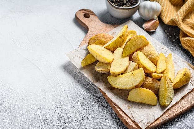 Quartiers de pommes de terre frites surgelés sur une planche à découper en bois.