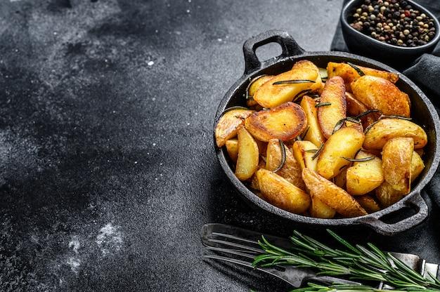 Quartiers de pommes de terre frits, frites dans une poêle. fond noir. vue de dessus. espace copie