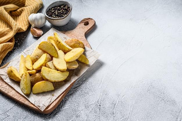 Quartiers de pommes de terre surgelés sur une planche à découper. recette de frites. fond blanc. vue de dessus. espace copie