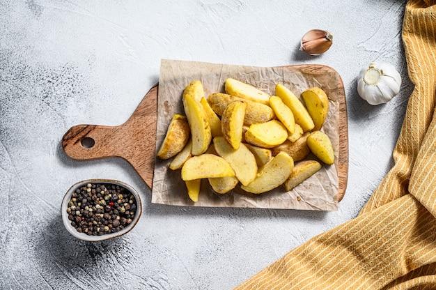 Quartiers de pommes de terre surgelés sur une planche à découper. recette de frites. fond blanc. vue de dessus