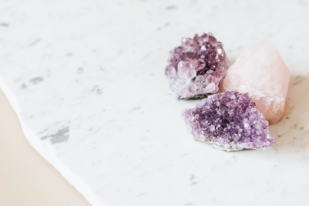Quartz rose et cristaux de guérison d'améthyste sur un comptoir en marbre