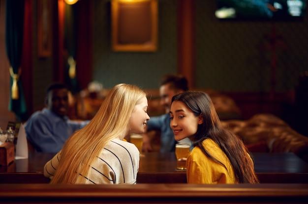 Quatre amis boivent de l'alcool et parlent au bar. groupe de personnes se détendre dans un pub, mode de vie nocturne, amitié, célébration de l'événement