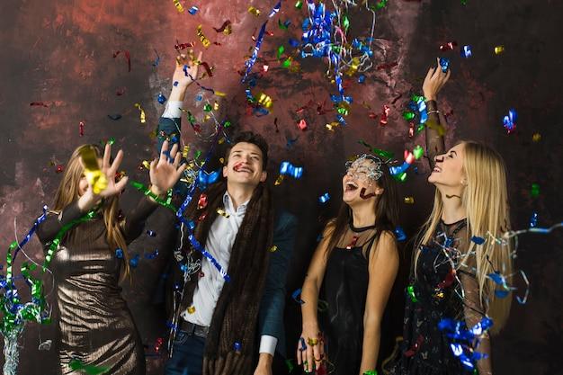 Quatre amis célébrant 2018 avec des confettis