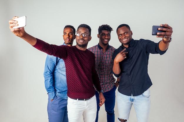 Quatre amis drôles de blogueurs afro-américains prenant selfie en studio sur fond blanc