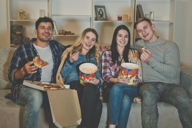 Les quatre amis avec un pop-corn et une pizza regardent un film sur le canapé