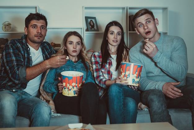 Les quatre amis avec un pop-corn regardent un film d'horreur sur le canapé
