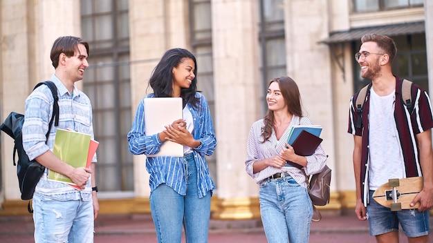 Quatre amis avec des sacs à dos sur leurs épaules et des cahiers