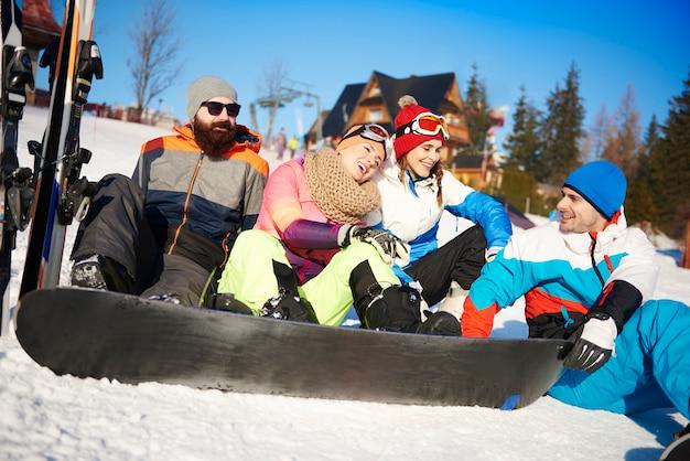 Quatre amis avec des snowboarders sur la neige